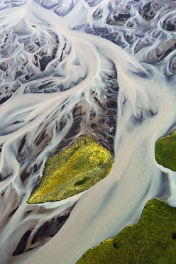Aerial image of a green island in an Icelandic river