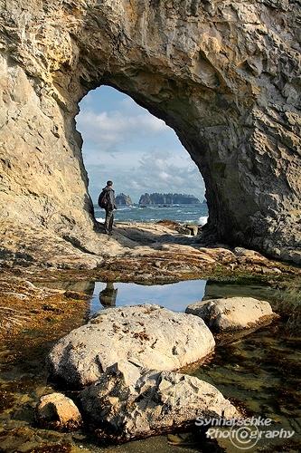 hiker at hole in the wall at rialto beach